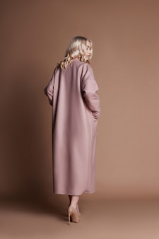 Beautiful blonde woman posing in a pink coat