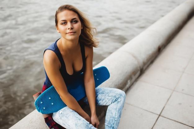 Beautiful blonde woman posing with a skateboard