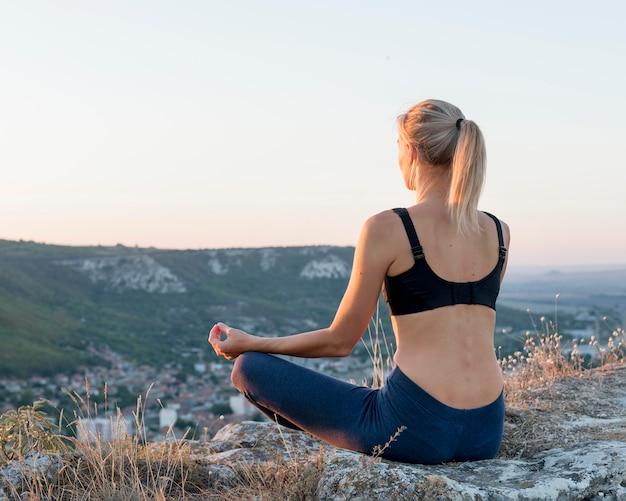 Beautiful blonde woman practicing yoga outdoors