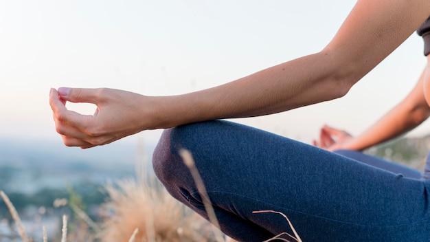Bella donna bionda a praticare yoga all'aperto