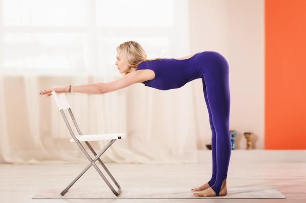 ヨガを練習している美しいブロンドの女性は椅子でuttanasana運動を行います Premium写真