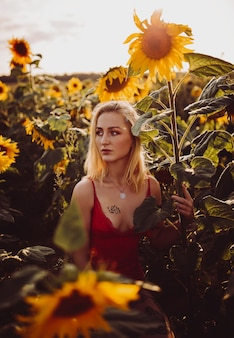 Beautiful blonde woman in a red dress in the field of sunflowers