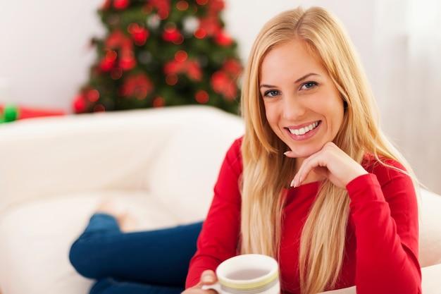 Bella donna bionda che si distende sul divano nel periodo natalizio