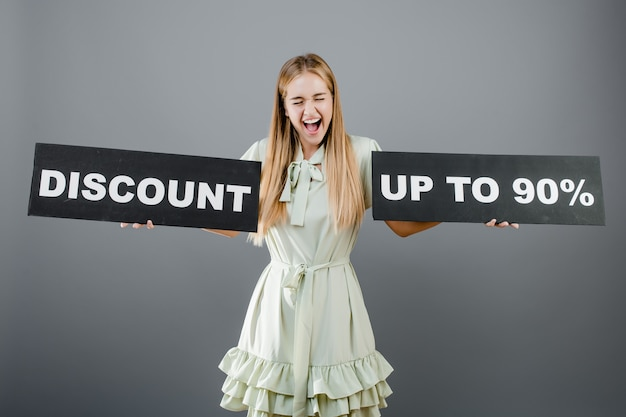 Beautiful blonde woman screaming with discount up to 90% sign isolated over grey