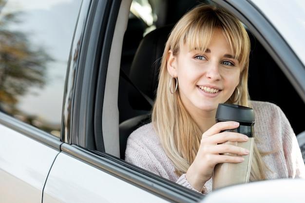 Beautiful blonde woman sitting in car