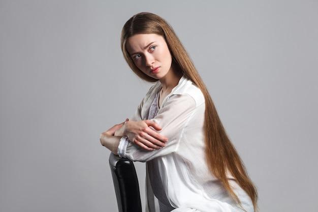 Beautiful blonde woman sitting on gray background