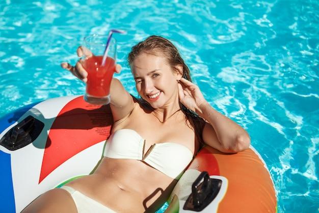 笑みを浮かべて、カクテルを飲み、プールで泳いでいる美しいブロンドの女性