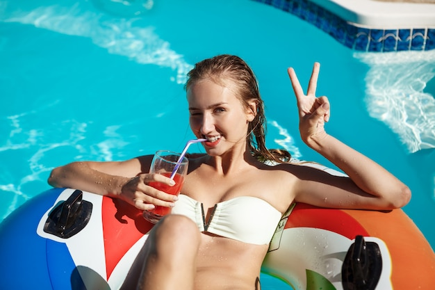 Beautiful blonde woman smiling, drinking cocktail, swimming in pool