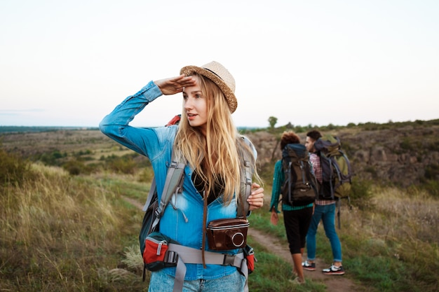 Beautiful blonde woman smiling, looking into distance, friends tourists background