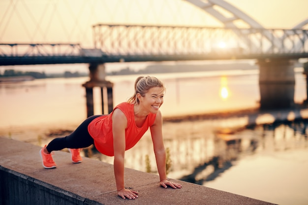 Beautiful blonde woman in sportswear with healthy habits doing push ups on quay.