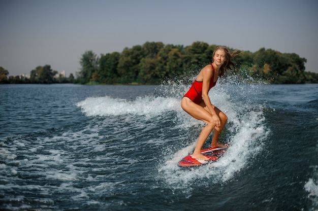 Beautiful blonde woman surfer riding down the blue splashing wave