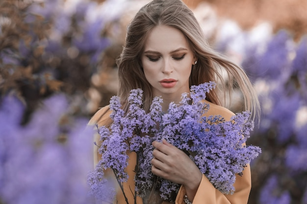 Beautiful blonde woman surrounded by blue flowers