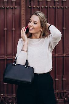 거리에 걸어 전화 통화하는 아름 다운 금발 여자. 어두운 캐주얼 바지와 크림 스웨터에 세련 된 웃는 비즈니스 여자의 초상화. 패션 컨셉. 여성 비즈니스 스타일. 높은 해상도.