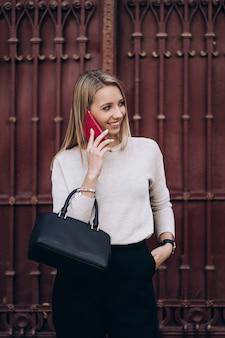 거리에 걸어 전화 통화하는 아름 다운 금발 여자. 어두운 캐주얼 바지와 크림 스웨터에 세련 된 웃는 비즈니스 여자의 초상화. 패션 컨셉. 여성 비즈니스 스타일.