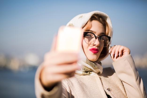 スマートフォンで自分撮りをしている美しいブロンドの女性の観光客。女性はショールと眼鏡をかけています