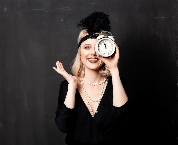 Beautiful blonde woman in twenties years clothes with alarm clock