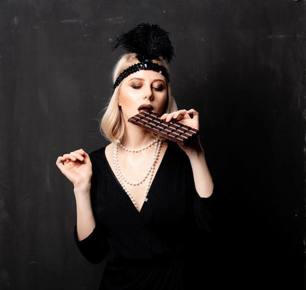 Beautiful blonde woman in twenties years clothes with chocolate slice