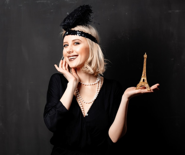 Beautiful blonde woman in twenties years clothes with eiffel tower statue