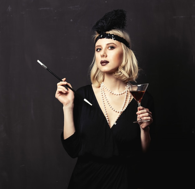 Beautiful blonde woman in twenties years clothes with smoking pipe and cocktail on dark background