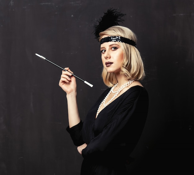 Beautiful blonde woman in twenties years clothes with smoking pipe on dark background