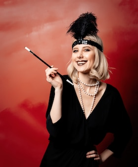 Beautiful blonde woman in twenties years clothes with smoking pipe on red background