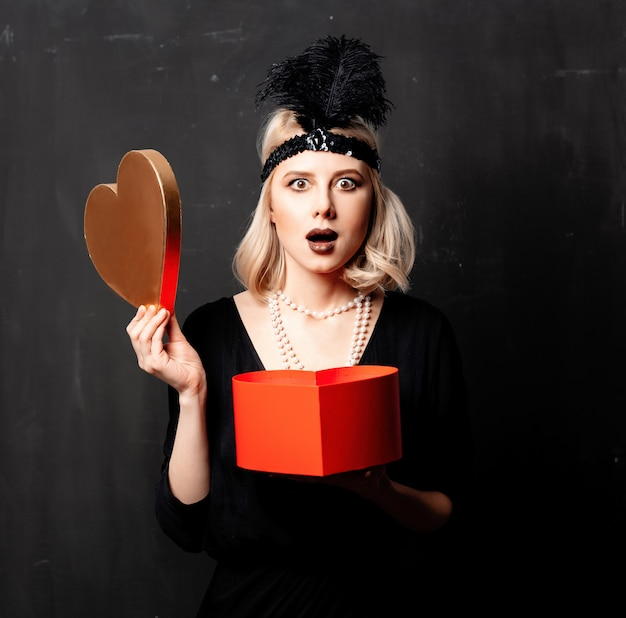 Beautiful blonde woman in twenties years clothes with valentine day gift