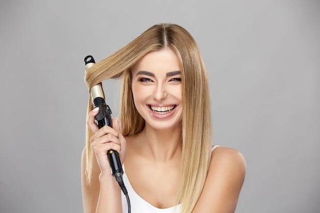 Красивая блондинка женщина использует щипцы для завивки для своих здоровых длинных волос и улыбается в камеру, удивительно счастливая женщина делает прическу