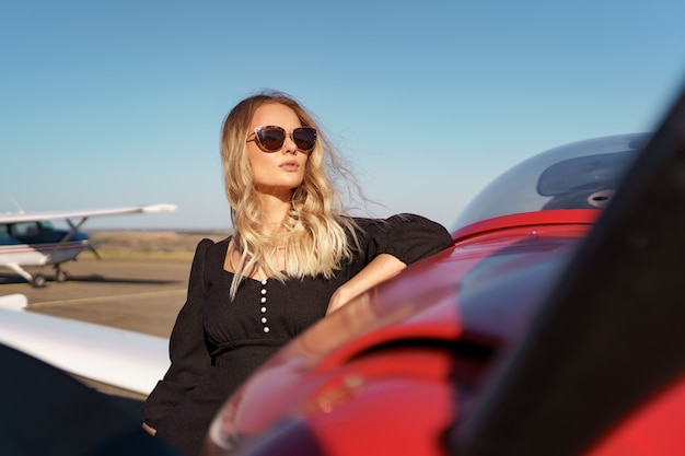 Beautiful blonde woman wearing modern sunglasses posing near a red private plane with sky