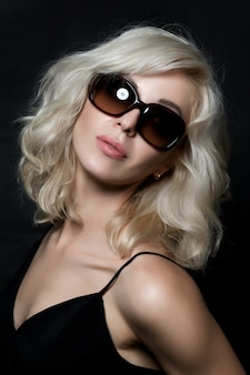 Beautiful blonde woman wearing sunglasses posing. model tests. fashion.