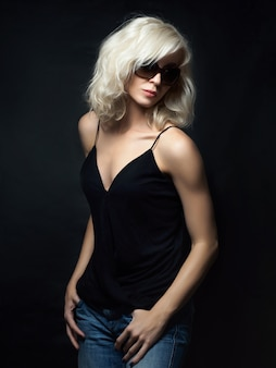 Beautiful blonde woman wearing sunglasses posing. model tests. fun fashion