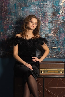 美しいブロンドの女性はレトロなfmレシーバーとスタジオでポーズをとってファッショナブルなドレスを着ています