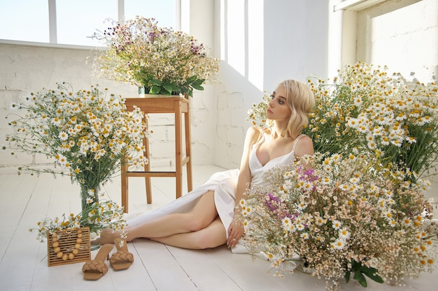 Beautiful blonde woman in a white dress is sitting on the floor among the chamomile flowers. portrait of a girl with a bouquet of wild flowers