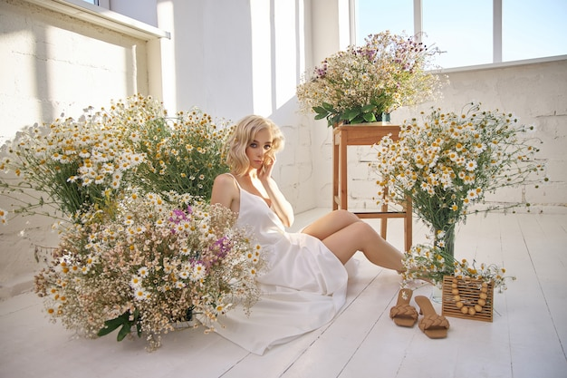 Beautiful blonde woman in a white dress is sitting on the floor among the chamomile flowers
