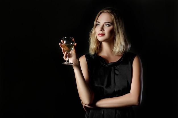 검정색 배경에 화이트 와인 한 잔과 함께 아름다운 금발의 여자