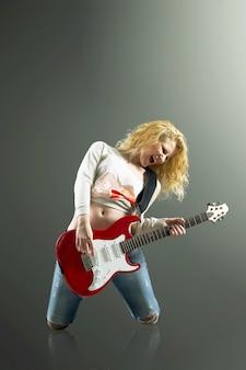 기타와 함께 아름 다운 금발의여자가 록 노래를 노래