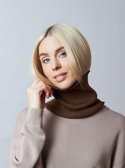 Красивая белокурая женщина с шарфом snood вокруг ее шеи. девушка в весенней одежде, теплый свитер