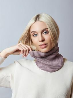 Красивая белокурая женщина с шарфом snood вокруг ее шеи. женщина в весенней одежде, теплый свитер