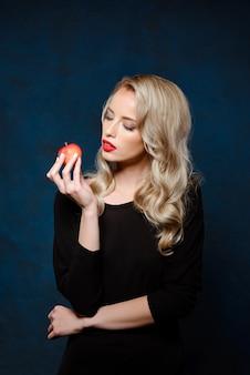 Bella donna bionda con trucco luminoso nella mela nera della tenuta del vestito