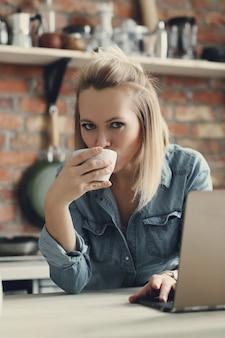 コーヒーカップとラップトップの美しいブロンドの女性