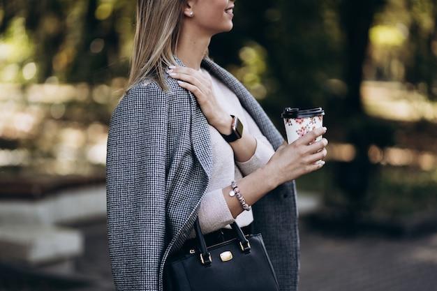 通りにコーヒーのカップを持つ美しい金髪の女性。コーヒーの紙コップを持つ女性の手は奪います。ファッションのコンセプトです。女性のビジネススタイル。高解像度。コーヒーメニュー