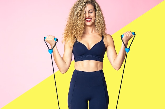 Beautiful blonde woman with curly hair is doing exercises and stretching with rubber bands