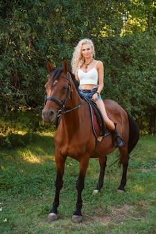 日中公園で馬に座っている巻き毛の美しいブロンドの女性