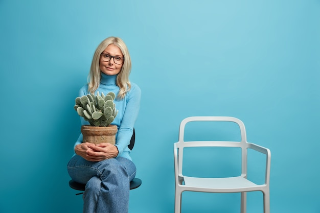 Beautiful blonde woman with european appearance holds pot of cactus sits alone near empty chair being on self isolation at home needs live communication