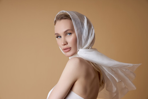 Beautiful blonde woman with a large white headscarf