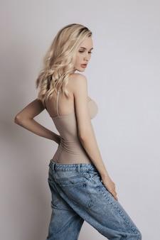 ジーンズに長い髪の美しい金髪の女性。足の長い細い女の子、減量、完璧な体型