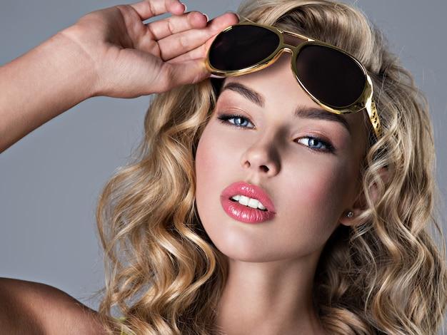 Bella donna bionda con lunghi capelli ondulati. attraente ragazza indossa occhiali da sole alla moda. giovane ragazza adulta sexy che propone allo studio - ritratto del primo piano