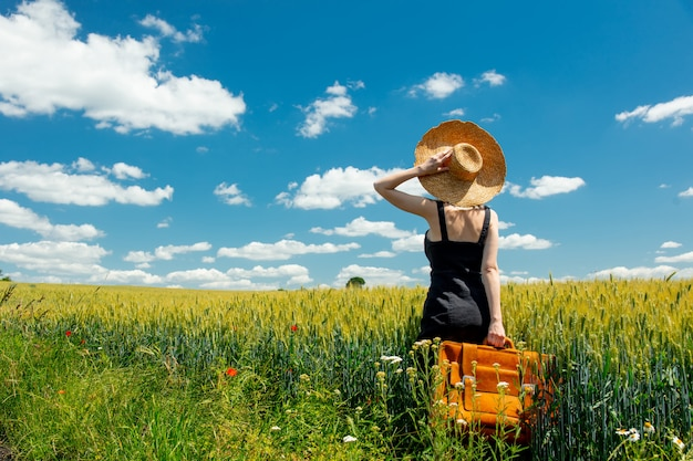 Beautiful blonde woman with suitcase in countryside road near wheat field