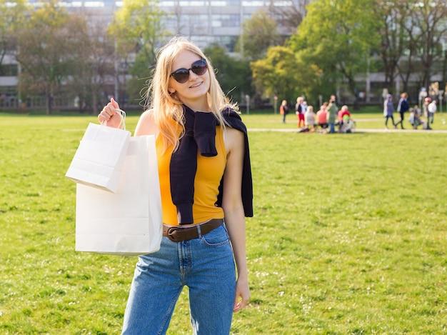 Красивая белокурая женщина в солнечных очках наслаждается покупками. потребительство, шоппинг макет