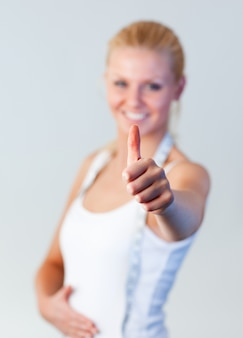 美しいブロンドの女性は、親指で体重減少の後に親指を集中