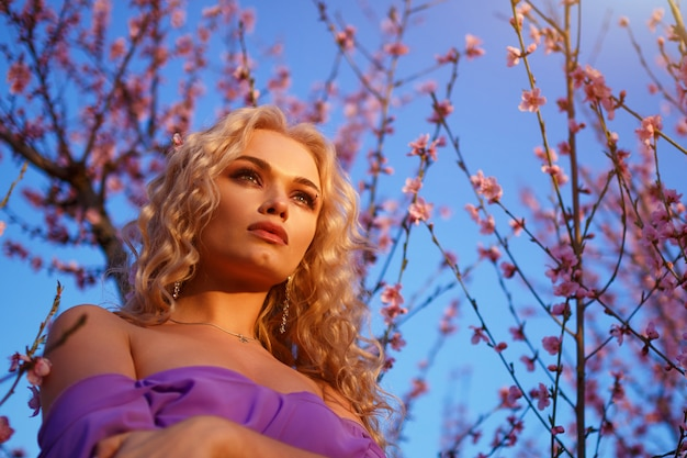 Beautiful blonde woman with wavy hair posing with blooming peach trees against the sky